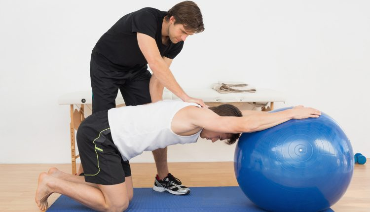 physical-therapist-assisting-young-man-with-yoga-ball-in-the-gym-at-hospital