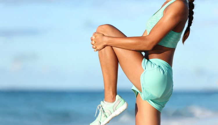 runner-body-closeup-doing-warm-up-routine-on-beach-before-running-stretching-leg-muscles