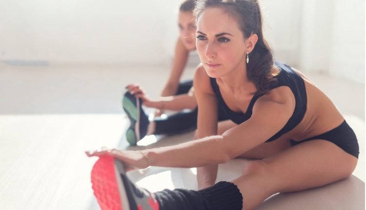 women-working-stretching-leg-muscles-of-back-to-warm-up-at-gym-fitness